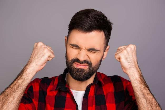 Молодой человек с гримасой на лице страдает от сильной боли
