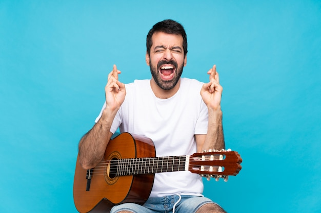 Young man with guitar over blue with fingers crossing
