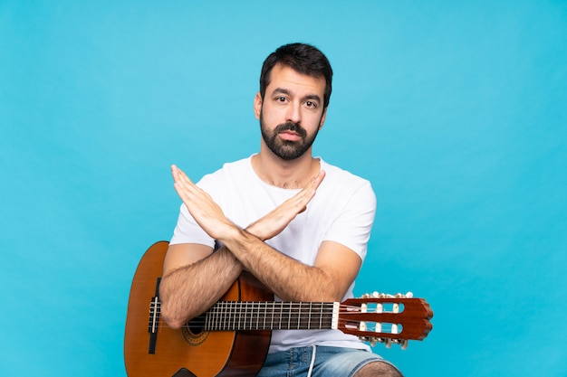 Young man with guitar over isolated blue  making no gesture