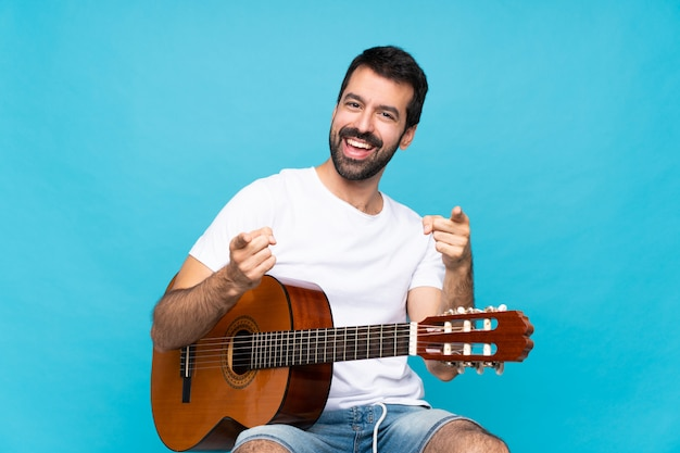 Young man with guitar over isolated blue  points finger at you while smiling