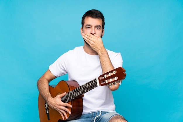 Young man with guitar over isolated blue wall covering mouth with hands