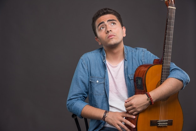 Молодой человек с гитарой, глядя на темном фоне. фото высокого качества