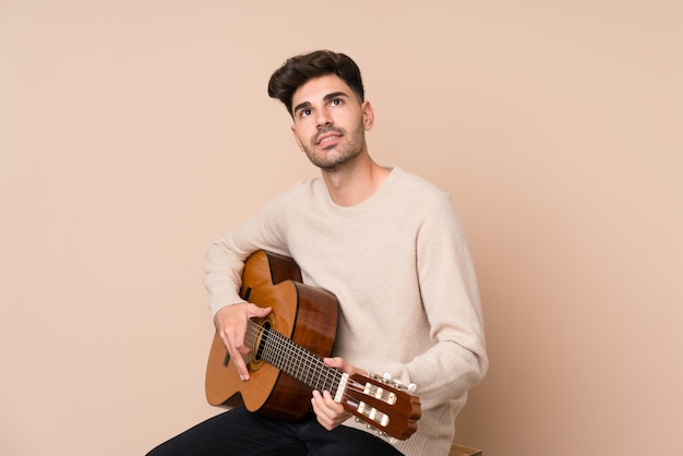 Young man with guitar looking up while smiling