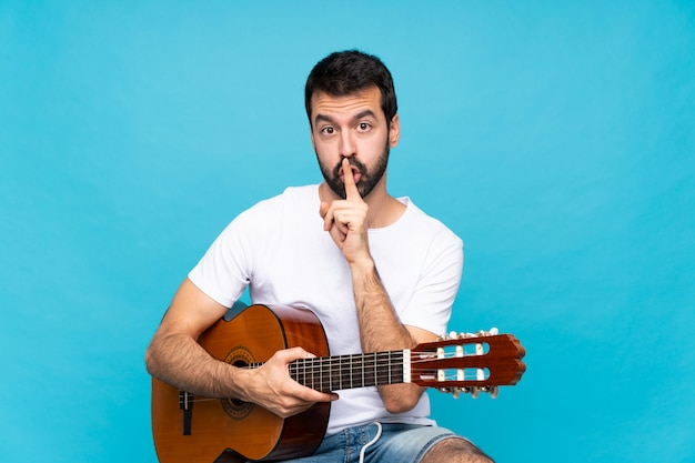 입에 손가락을 넣어 침묵 제스처의 표시를 보여주는 격리 된 파란색 위에 기타와 함께 젊은 남자