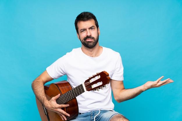 Молодой человек с гитарой над изолированным синим несчастным для чего-то не понять