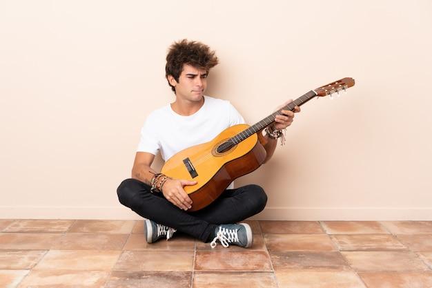 Молодой человек с гитарой сидит на полу