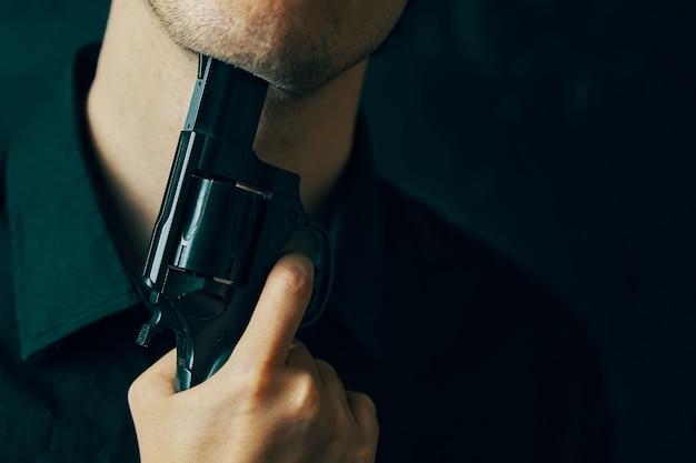 Young man with gun is preparing to commit suicide depression with fatal outcome guy in black shirt m...