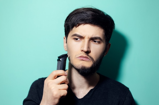 Young man with half shaved face, holding electric shaver trimmer on wall of aqua menthe color.