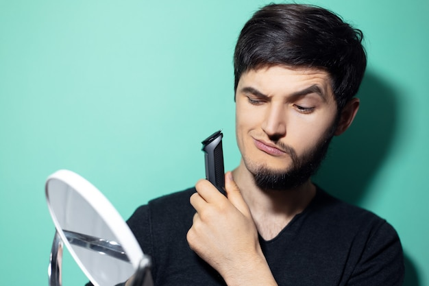 Young man with half shaved face, looking in mirror holding electric shaver trimmer on wall of aqua menthe color.
