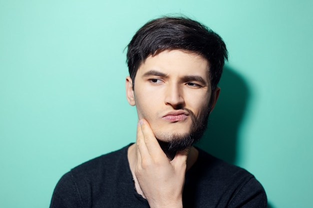 Young man with half shaved face touching chin on wall of aqua menthe color.
