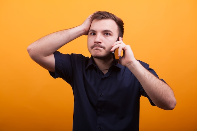 Young man with hand on his head while talking on the phone. irritated young man