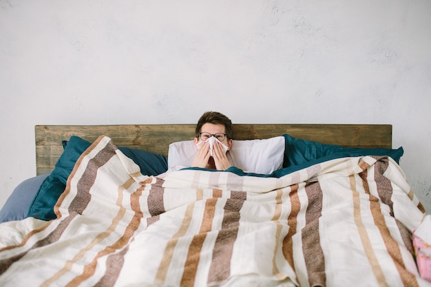Young man with handkerchief. sick guy on the bed has runny nose. man makes a cure for the common cold.