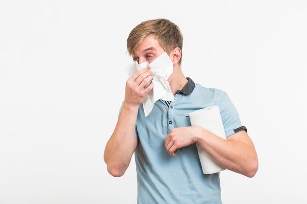 ハンカチ病人が孤立した若い男は白い壁に鼻水があります