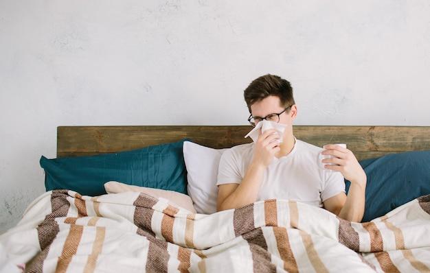 손수건으로 젊은 남자. 침대에있는 아픈 사람은 콧물이 있습니다. 사람은 감기를 치료합니다.
