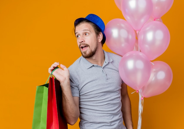 Giovane con un cappello che celebra la festa di compleanno che tiene i sacchetti di carta e gli aerostati che sorridono felice ed eccitato in piedi sopra la parete arancione