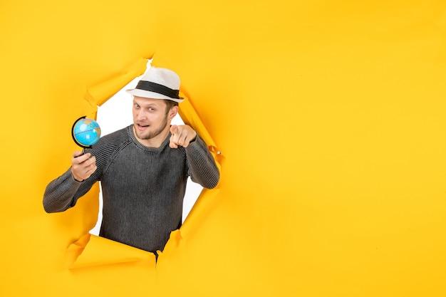 Giovane con un cappello che tiene un piccolo globo e che punta in avanti in un muro strappato sul giallo