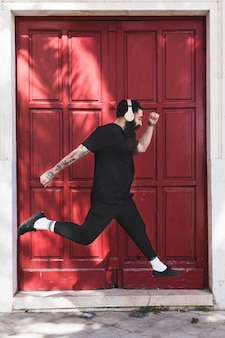 Young man with headphone on his head jumping against closed red door