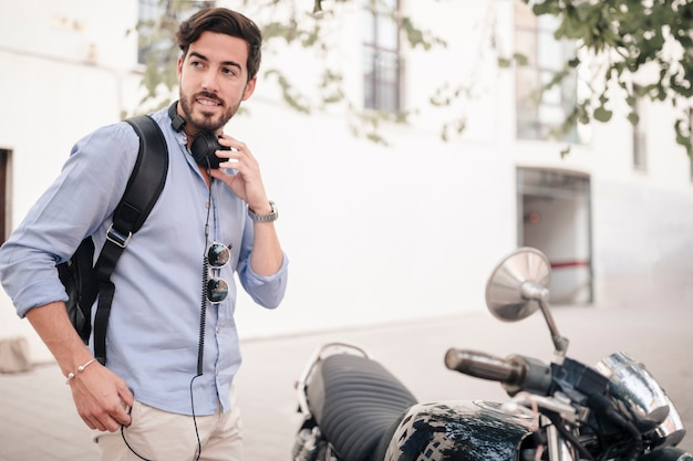 Young man with headphone standing near motorbike