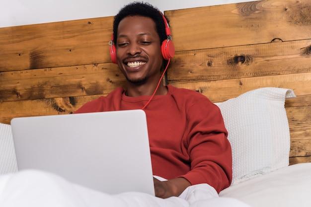 ヘッドフォンとラップトップを使用して若い男