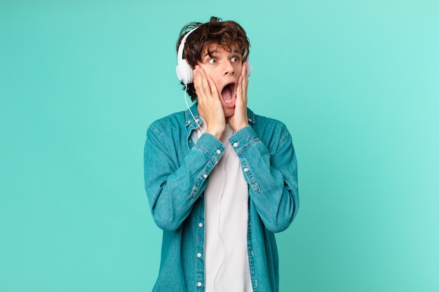 Young man with headphones feeling happy, excited and surprised