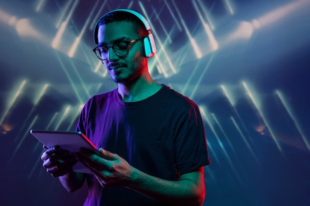 Young man with headphones holding digital tablet in front of himself while watching video among neon lights in isolation
