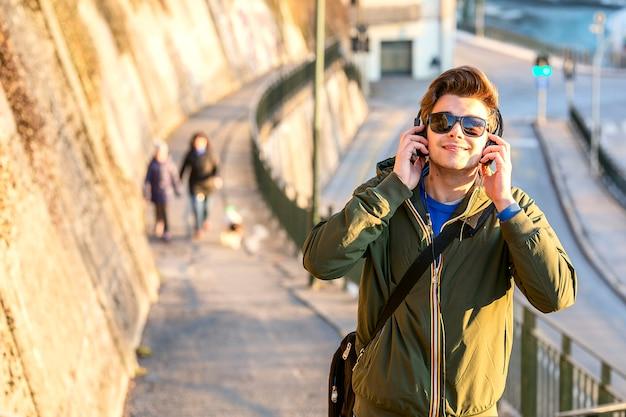 Молодой человек с наушниками на улице