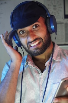 A young man with headphones listning music and not enjoying