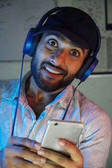 A young man with headphones listning music and enjoying