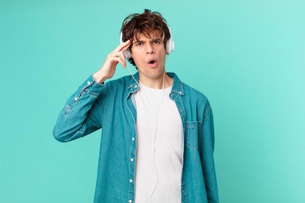 驚いたように見える、新しい考え、アイデア、または概念を実現するヘッドフォンを持つ若い男