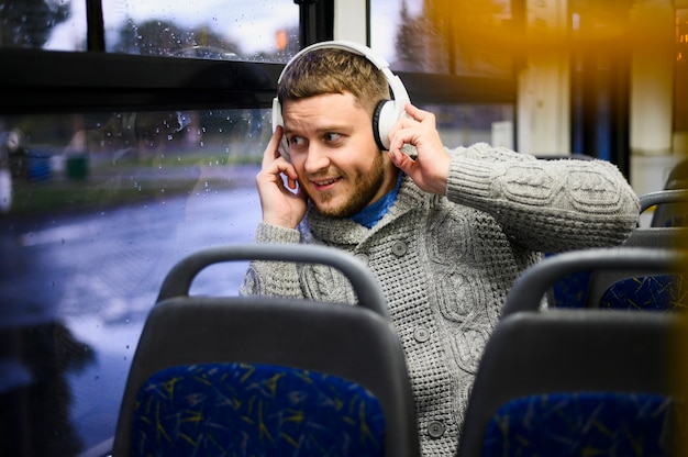 Young man with headphones on the seat of the bus