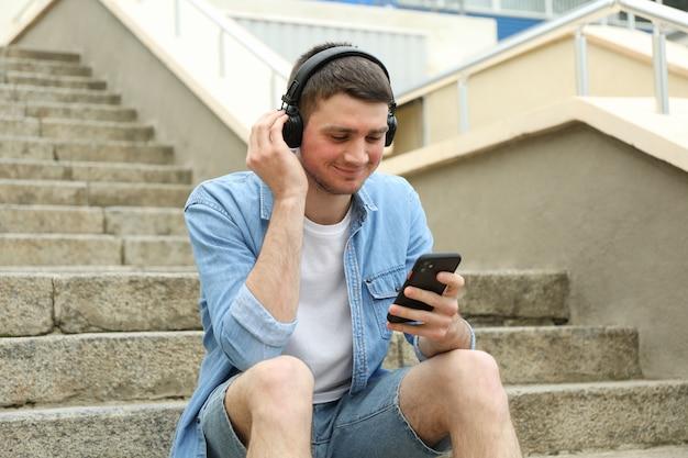 Молодой человек в наушниках сидит на лестнице и смотрит на свой телефон