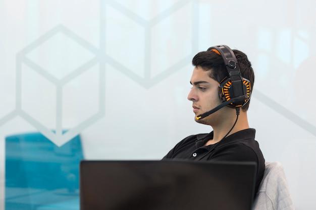 コワーキングオフィスに座っているヘッドフォンと若い男。