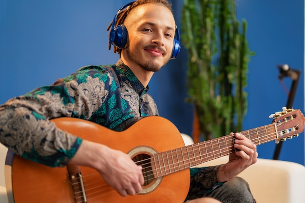 Young man with headphones sitting on sofa and playing guitar