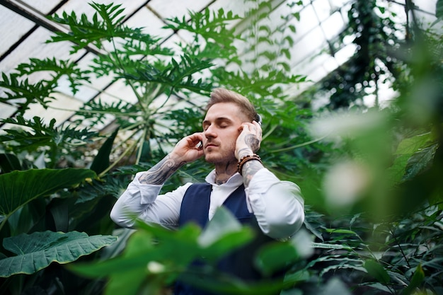 Young man with headphones standing in botanical garden, listening to music. green bussiness concept.