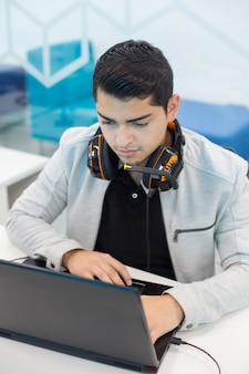 コワーキングオフィスのコンピューターで作業して、ヘッドフォンと若い男。