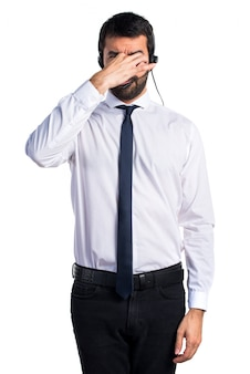 Young man with a headset doing smelling bad gesture