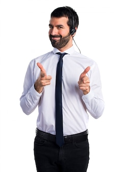 Young man with a headset pointing to the front