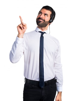 Young man with a headset pointing up