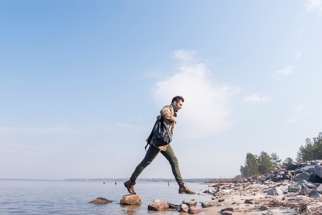 Young man with his backpack on shoulder jumping over the stones near the lake