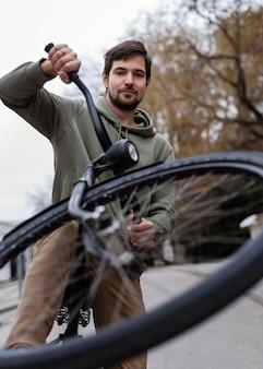 公園で自転車を持っている若い男