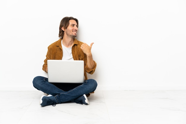 Young man with his laptop sitting one the floor pointing to the side to present a product