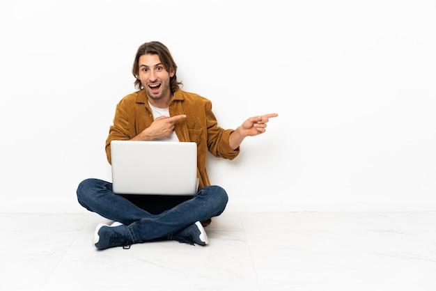 Молодой человек со своим ноутбуком сидит на полу с удивлением и указывает сторону