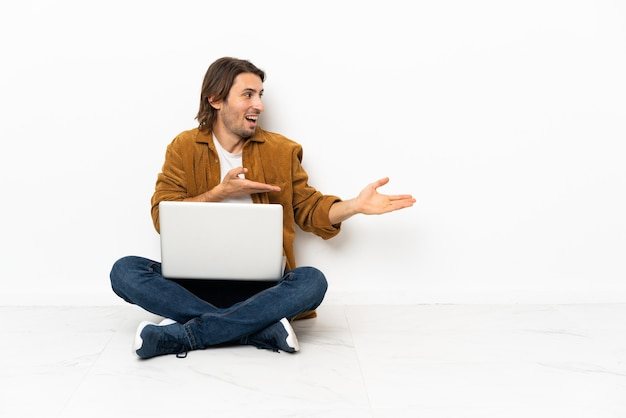Молодой человек со своим ноутбуком сидит на полу с удивленным выражением лица