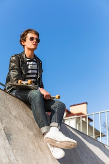 Young man with his skateboarding at the skate park