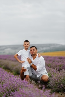 A young man with his young son is walking through a beautiful field of lavender and enjoying the fragrance of flowers. rest and beautiful nature. unity with nature and harmony.