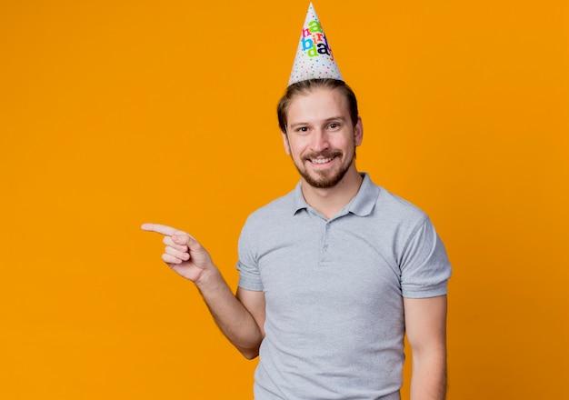 생일 파티를 축하하는 휴일 모자와 젊은 남자가 행복하고 쾌활한 오렌지 벽 위에 서있는 측면을 손가락으로 가리키는 미소