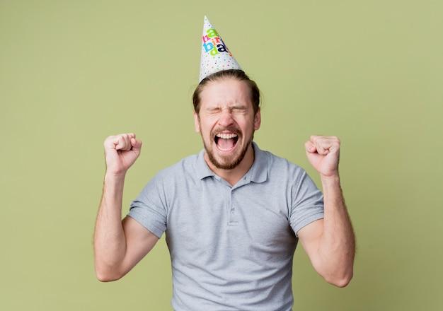 明るい壁の上で幸せで興奮して誕生日パーティーを祝うホリデーキャップを持つ若い男