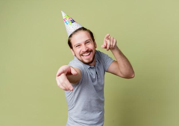 誕生日パーティーを祝うホリデーキャップを持つ若い男は、光に幸せで興奮しています