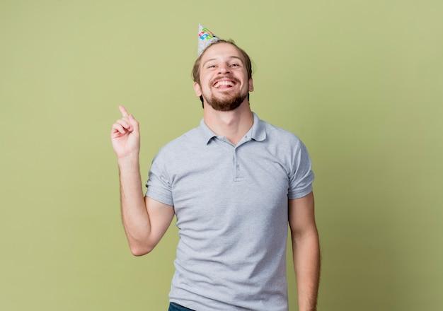 誕生日パーティーを祝うホリデーキャップを持つ若い男は、光の壁に人差し指を見せて幸せで興奮しています