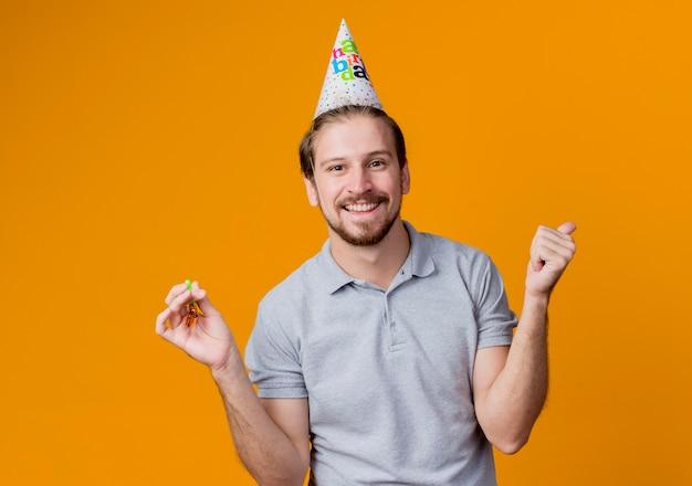 생일 파티를 축하하는 휴일 모자와 젊은 남자가 행복하고 흥분 오렌지 벽 위에 서 웃는